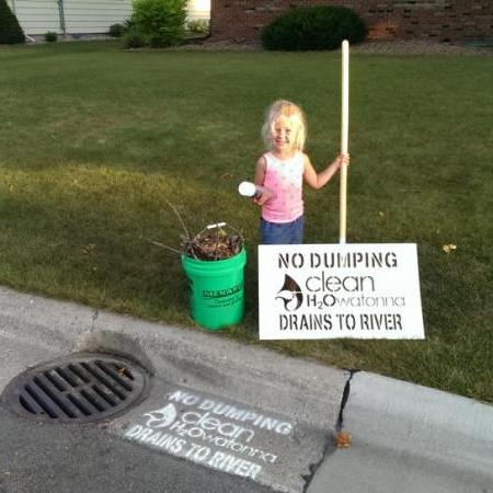 Small child by a sign that says No Dumping